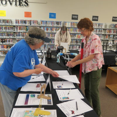 Pat, Trish and Nancy Sue organize bid sheets