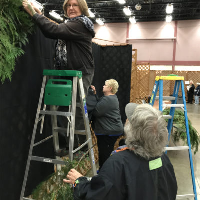 Pat hands boughs to Nancy as she works her magic trimming the booth.