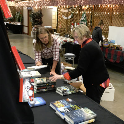 Ali and Judi sort books several hours before the Holiday Bazaar opens to the public.
