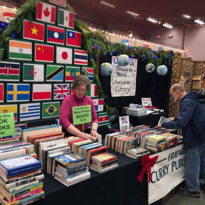 "2018 Judy and Jim sort books at our ""Christmas Around the World"" booth in 2018"