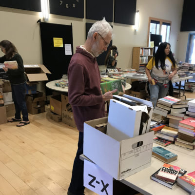 George sorting paperback fiction.